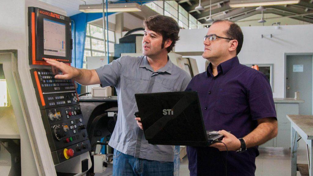 Professores Pablo Valle (à esq.) e Augusto Pescador lecionam para alunos de especialização no Laboratório de Fabricação, em Curitiba. Foto: Nicolle Schumacher/Sucom-UFPR, 2019
